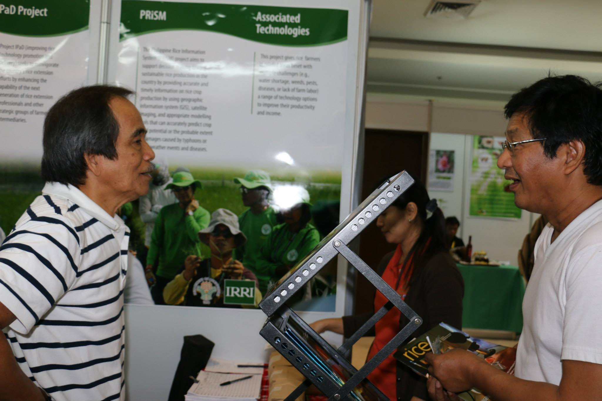 Dr. Manny Alejar talks to an exhibit visitor about IRRI's work in general.
